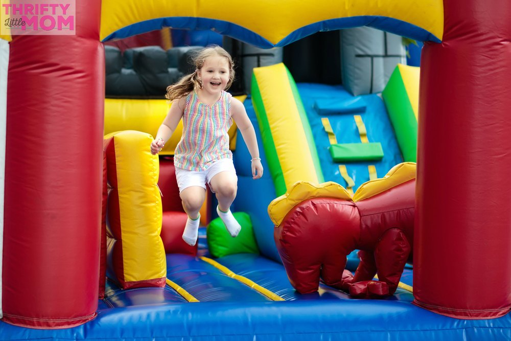 child in obstacle course bouncy house for 5th birthday