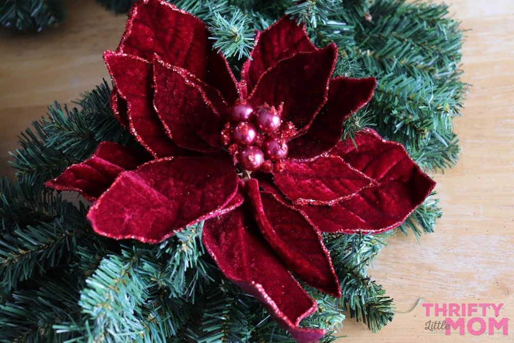 placing decorations on poinsettia decor wreath