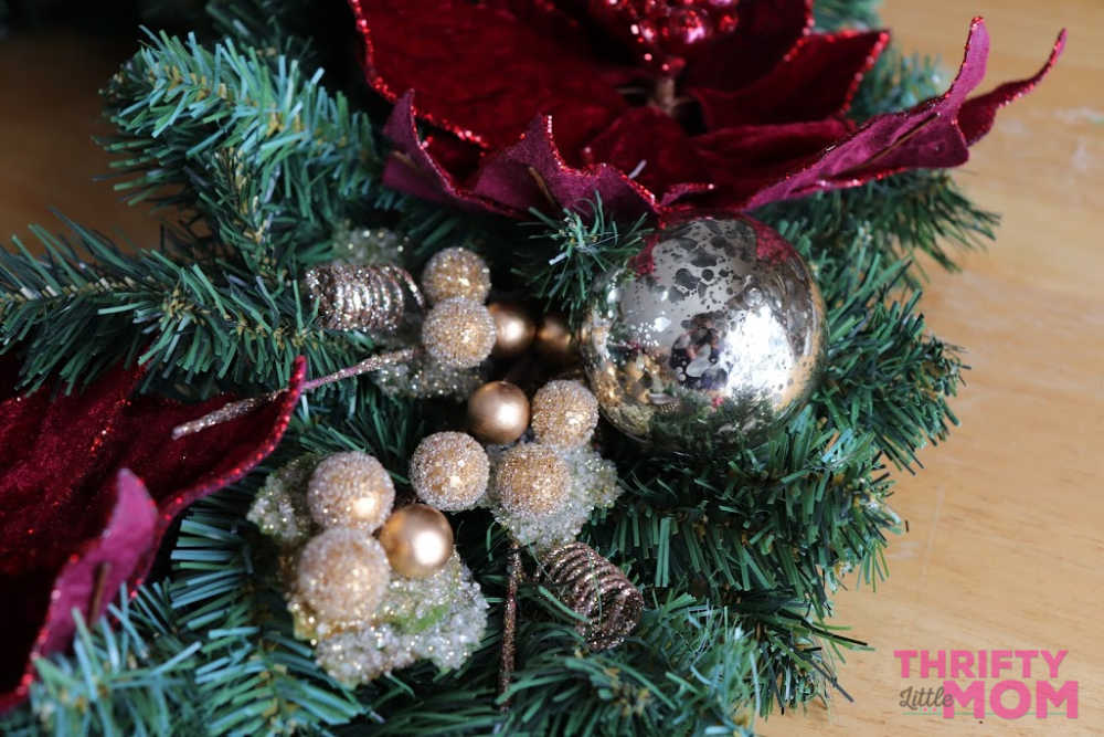 neatly tuck the ornaments into the poinsettia decor wreath under flowers