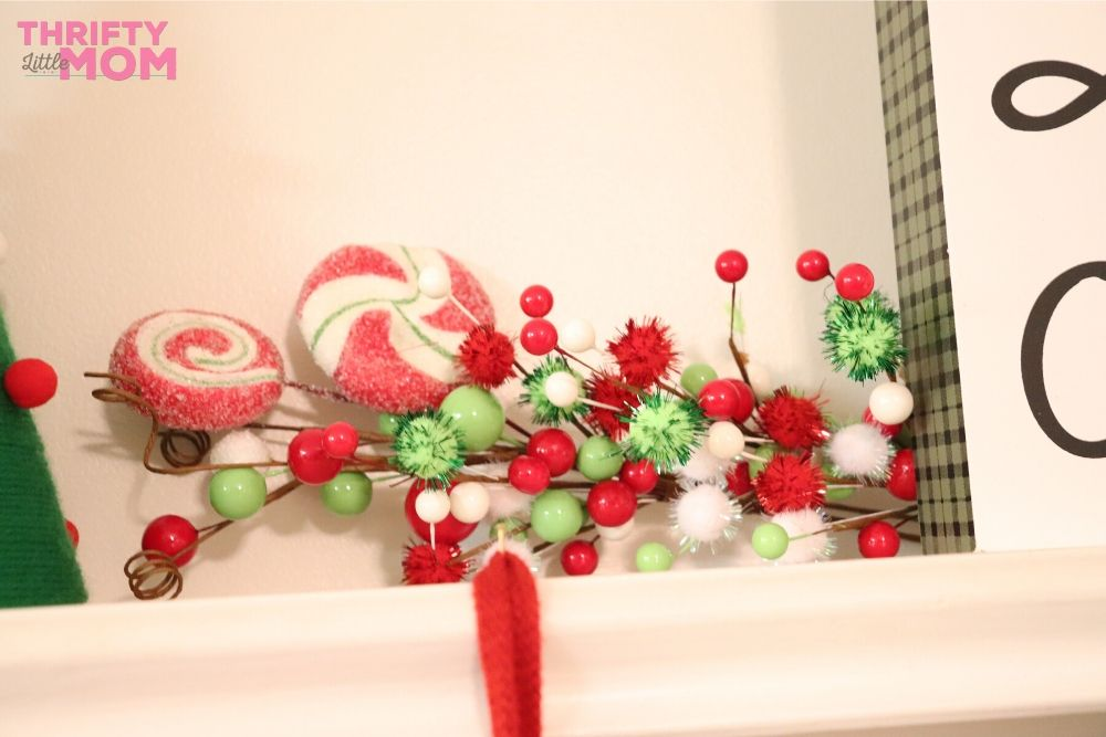 layering decorations on grinch fireplace mantle