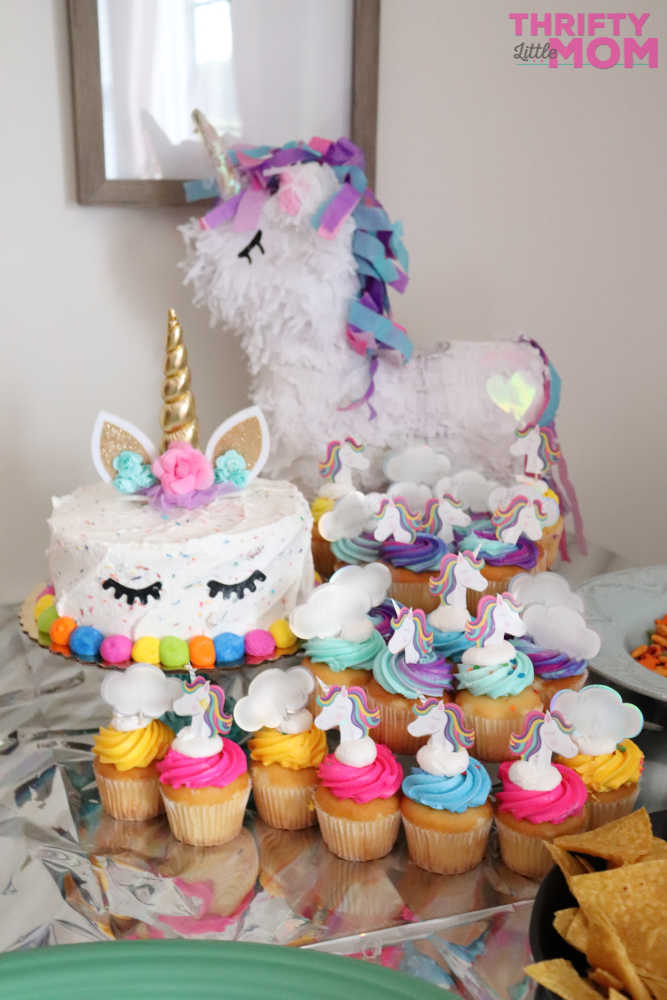 unicorn cake and cupcakes with matching balloons are perfect decoration for an 8 year old birthday party idea