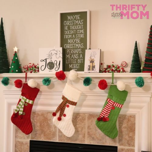 layered decorations for a grinch themed fireplace mantle