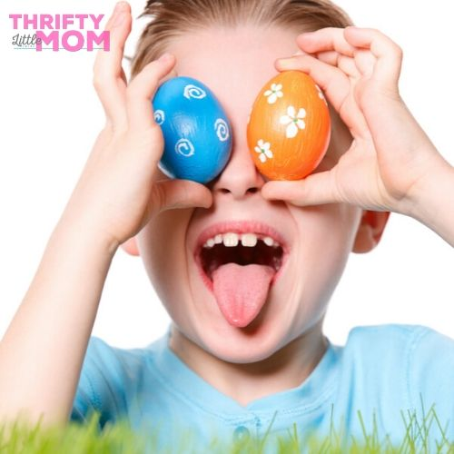 kid playing with two painted eggs for easter game