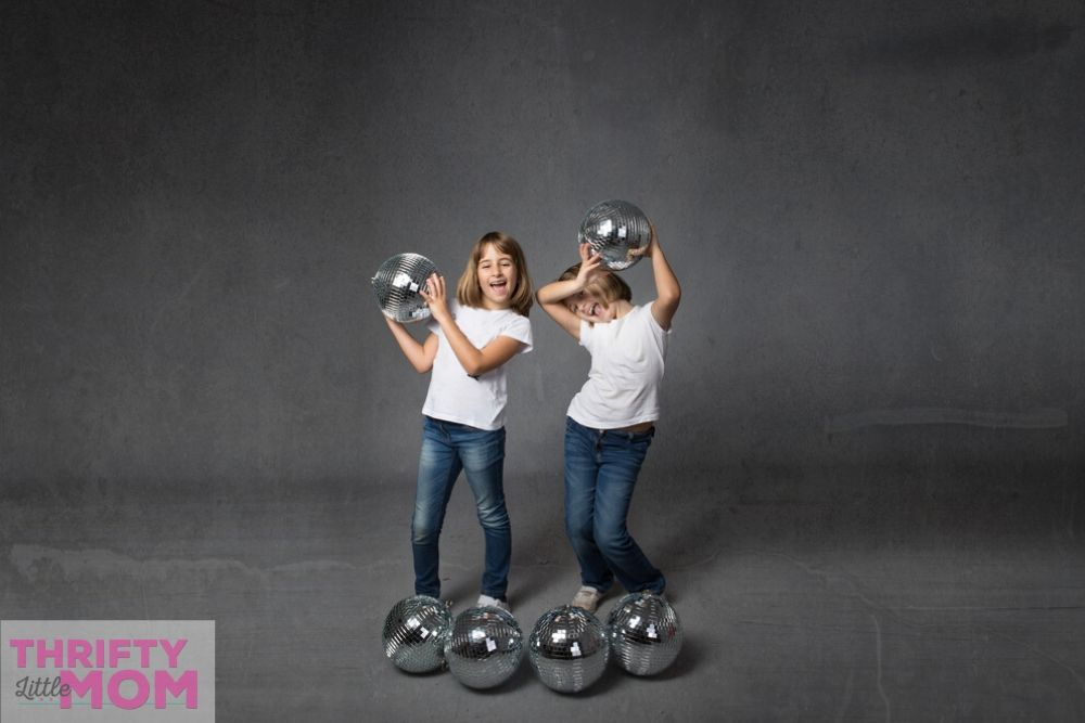 two kids playing with disco balls for a kids disco party